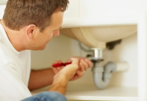Mature plumber fixing a problem in the sink